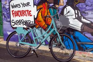 Bike share bike stood against graffiti