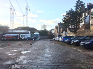 cars and coaches parked in empty urban site with cobbled road