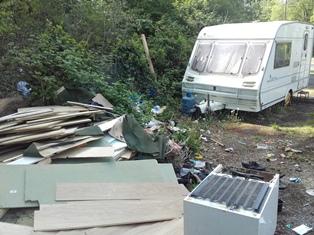 pile of building materials near white caravan