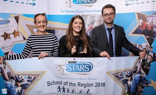 Nursery owner and others smiling behind banner proclaiming 'school of the region'