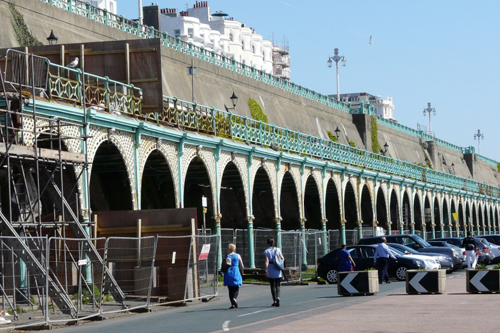 Two people walk along Madeira Drive, with Madeira Terraces above them. The terraces have scaffolding around them.
