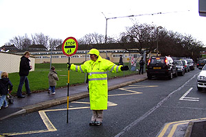 A School Crossing Patrol stopping traffic in the road