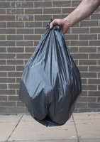 small image of someone holding a black refuse bag