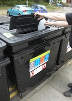 small image of someone using the block of flats recycling bins
