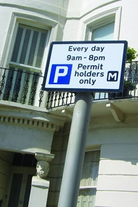 A sign showing the parking restrictions for a permit bay
