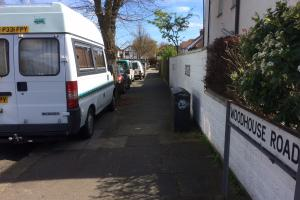 Vehicles parked on pavement in West Hove