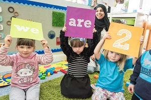 3 children hold signs that say 'We are 2'