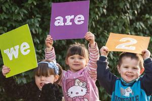 Free childcare for two year olds campaign banner - three children hold up signs saying we are two.