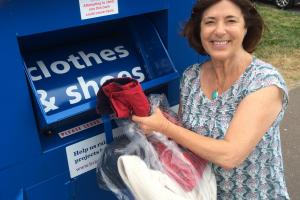 Councillor Gill Mitchell putting clothes in new textile recycling bank