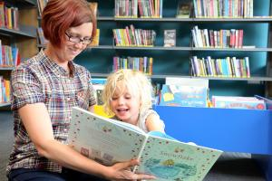 A women and girl read together at Mile Oak library