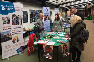 People talking at a One Journey Better event stand.