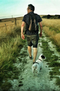 sport/healthwalks- man walking along dirt path with small black and white dog