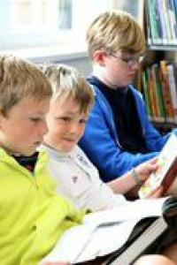 Three boys reading at Mile Oak library